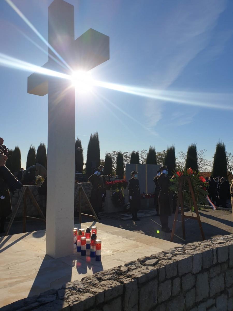 Svijeće i cvijeće pred osunčanim križem  u Škabrnji / Foto: Fenix (L.B.)